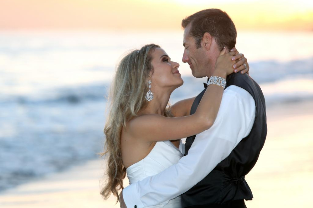 Couple hugging and kissing on the beach for their romantic destination wedding in Hawaii