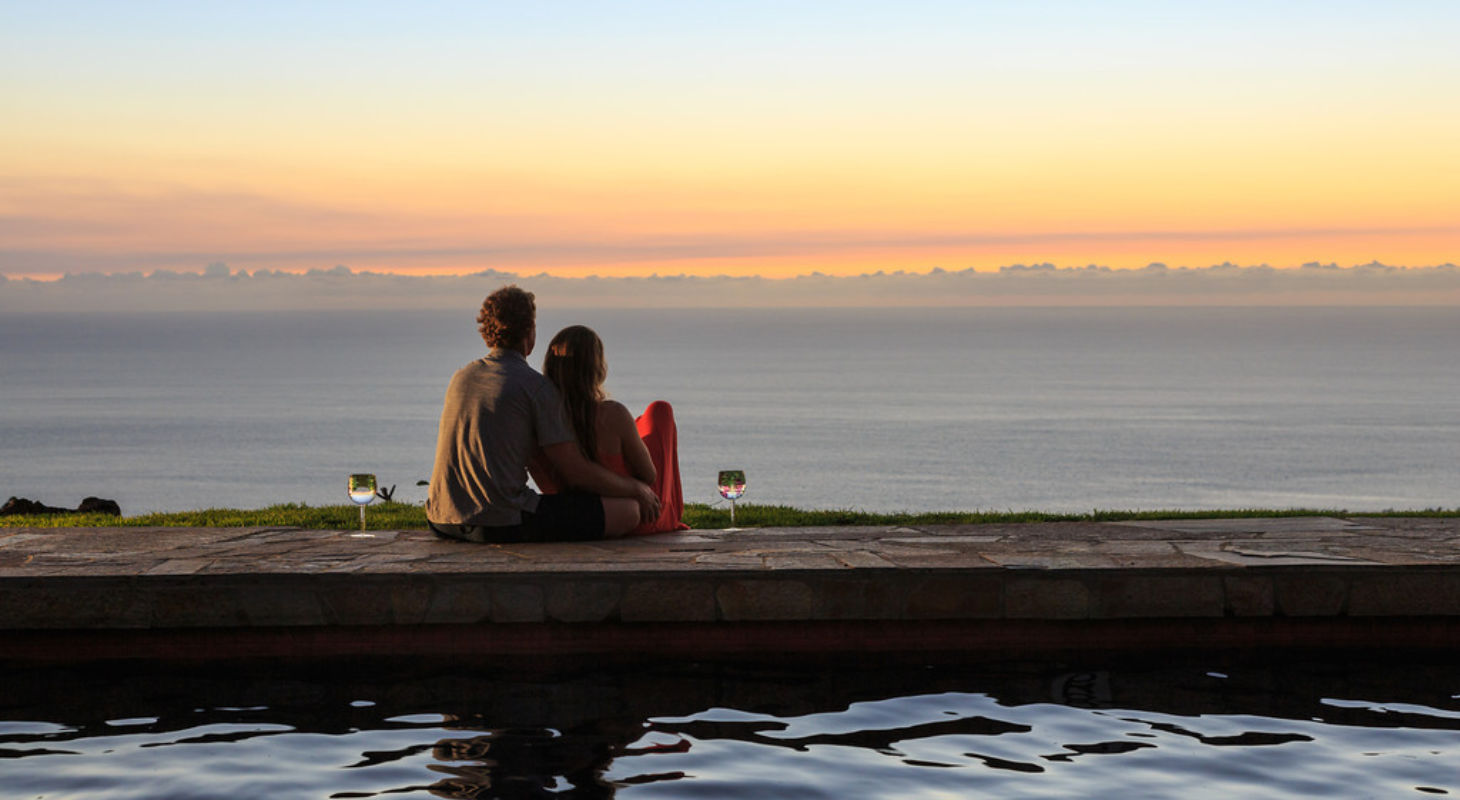 Couple enjoying sunset and wine at sunset for their Hawai'i elopement and Hawai'i honeymoon