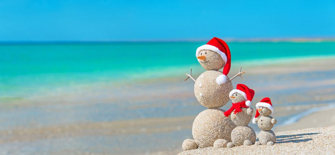 Snowmen on the beach with Santa hats