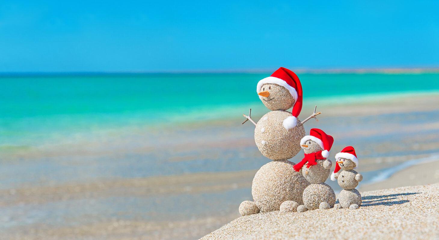 Snowmen on the beach with Santa hats