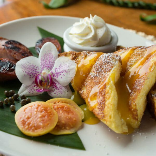 French Toast triangles with fruit and a flower at Big Island bed and breakfast