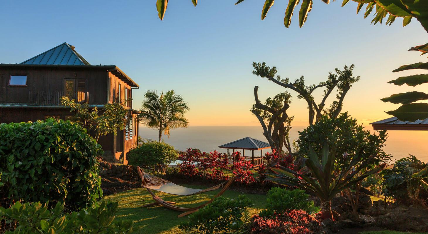 Holualoa gardens at sunset with hammock, flowers, and inn building