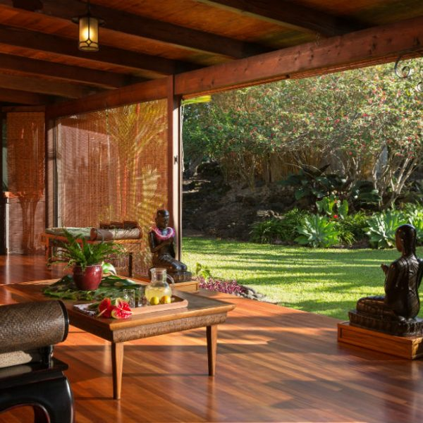 Zen statues in a living area with couch, table, and opening to a green lawn at our Hawaii B&B