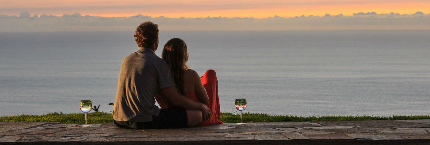 Couple sitting by hot tub watching the sunset over the ocean
