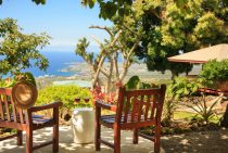 Patio overlooking Hawaii with chairs and wine