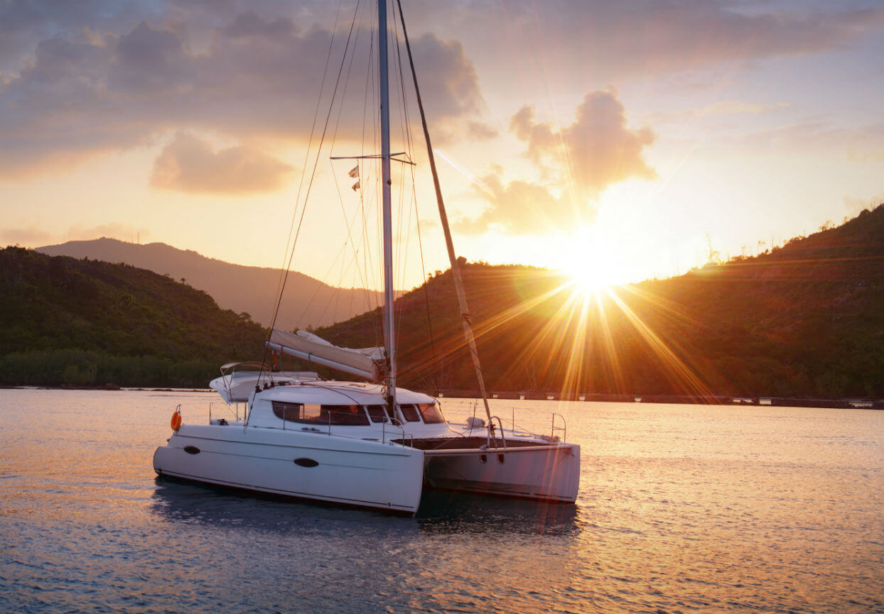 Catamaran boat on sea at sunset