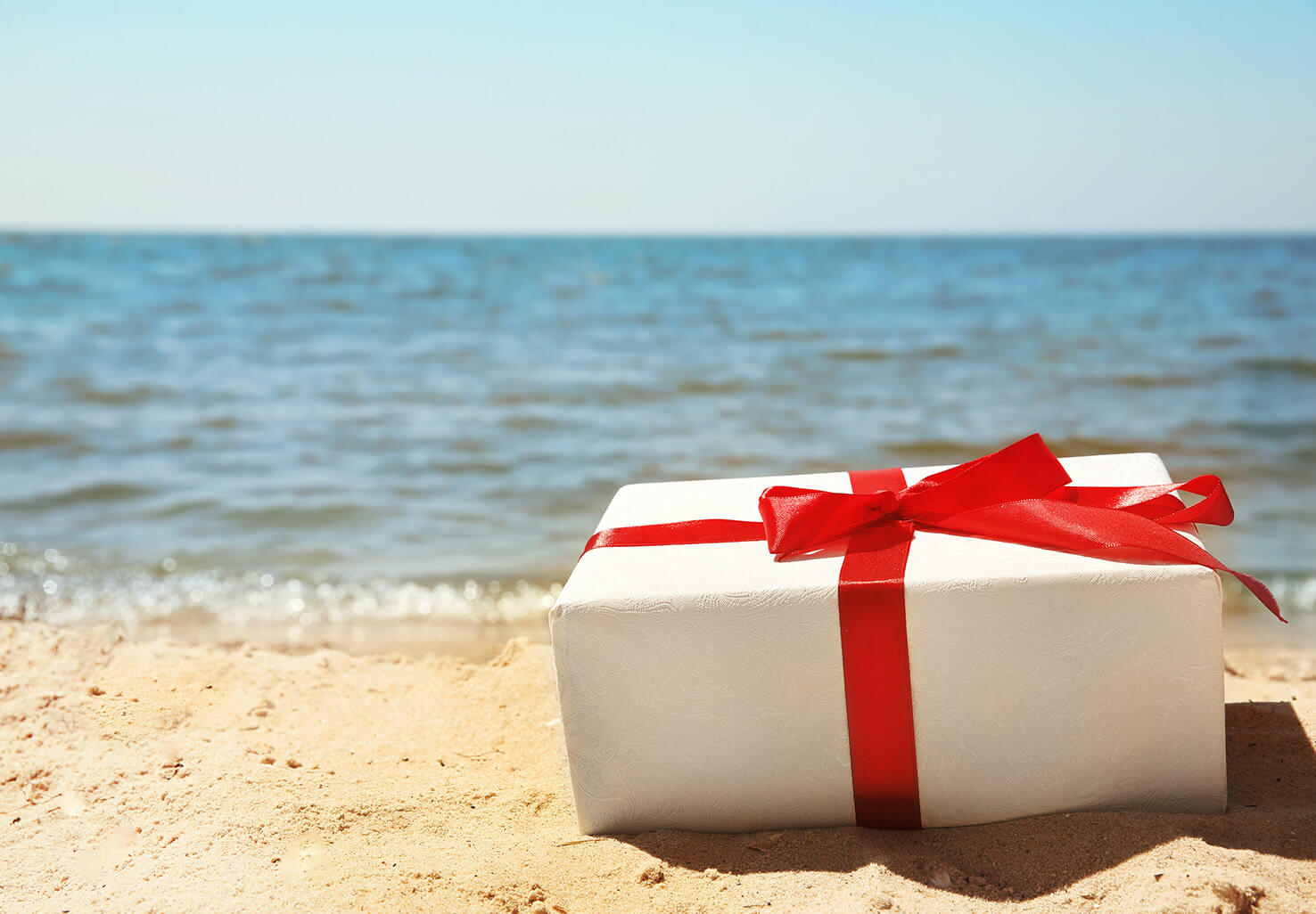 Gift with red ribbon on the beach