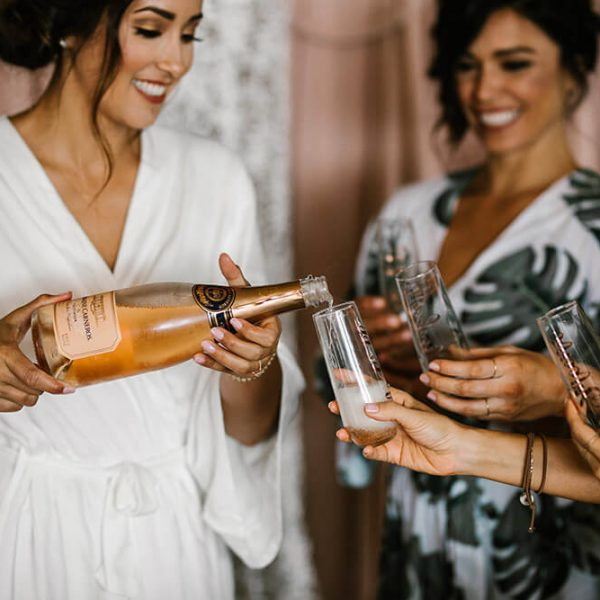Bride in bathrobe pouring champagne for bridesmaids while getting ready