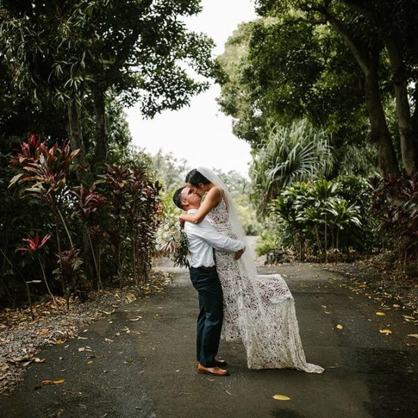 Bride and groom kiss and embrace on road through Hawaiian forest