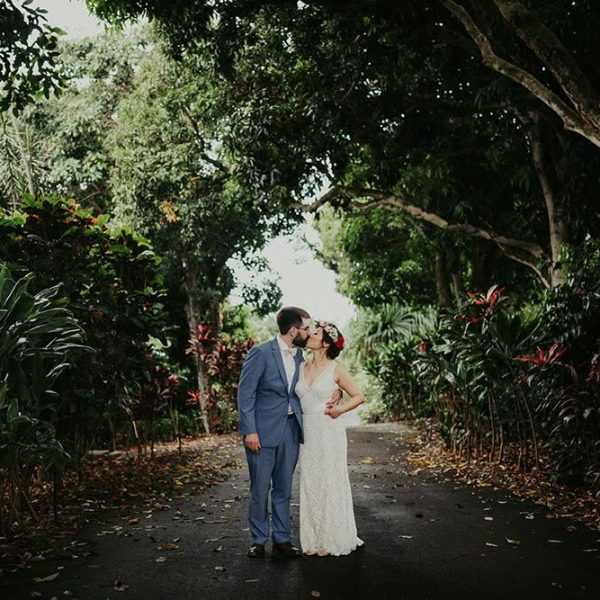Bride and groom kiss on road through Hawaiian forest