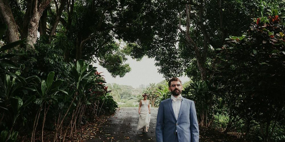 Bride walking up to groom on road through Hawaiian forest
