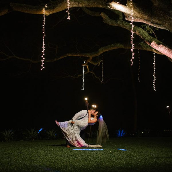 Groom kisses and sweeps bride up under tree with hanging lights