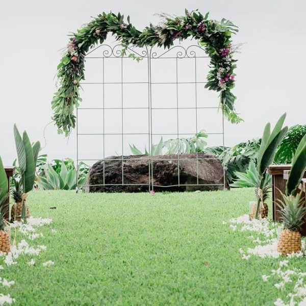 Wedding arch of tropical flowers on a trellis, seen from the aisle