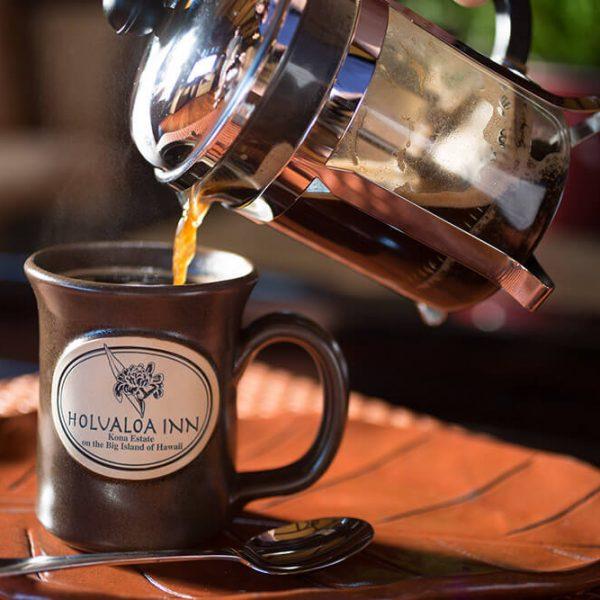 Pouring 100% Kona Coffee into a mug at our coffee estate in Holualoa Hawaii