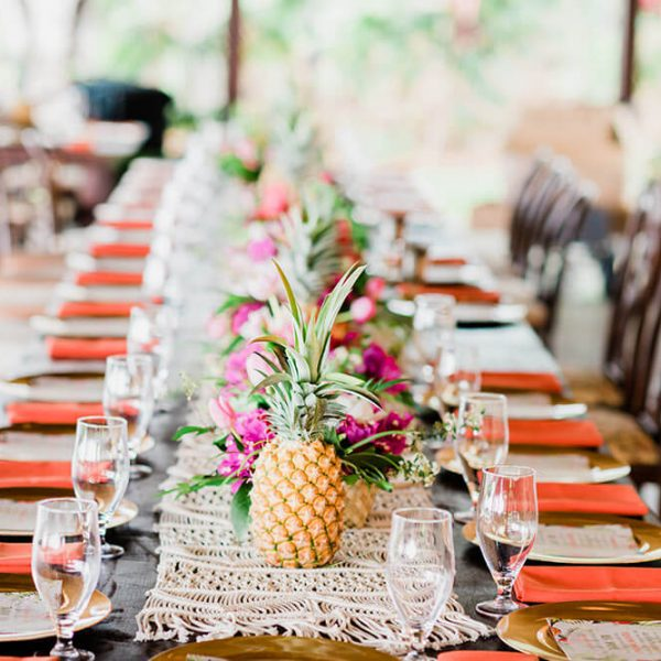 Dining table of Hawaiian wedding reception set with bright napkins and centerpiece of flowers with pineapples