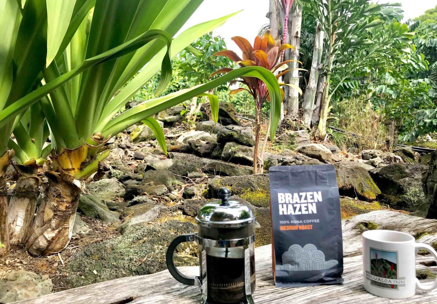 Brazen Hazen coffee, Holualoa Inn mug, and french press in tropical gardens