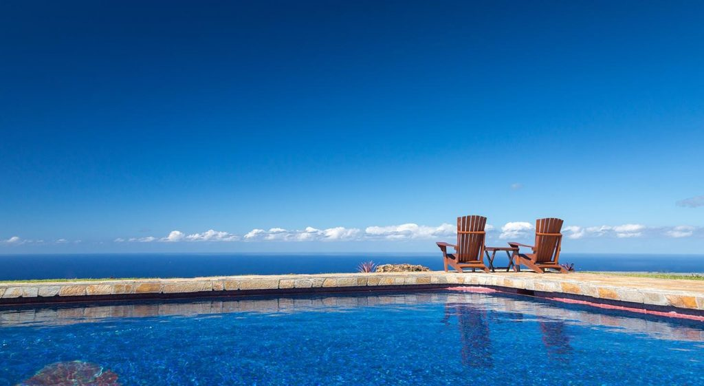 2 chairs by pool overlooking the ocean at Hawaii bed and breakfast