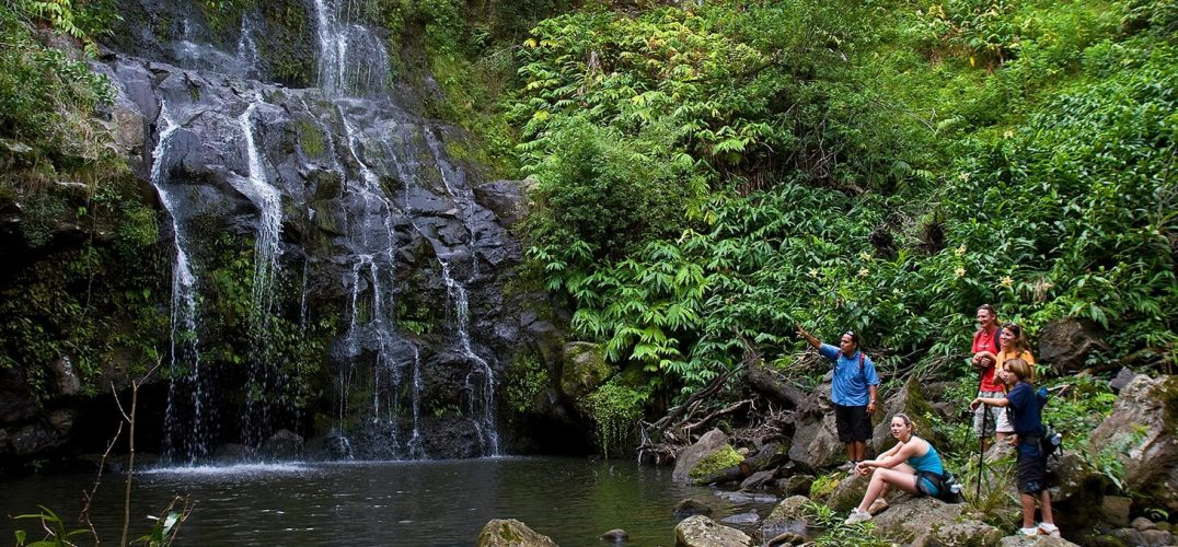 Hikers near a waterfall in Hawaii