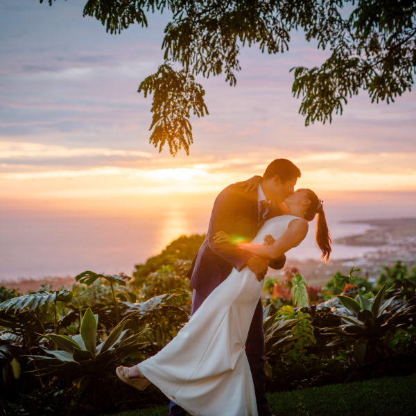 groom dips and kisses bride at sunset