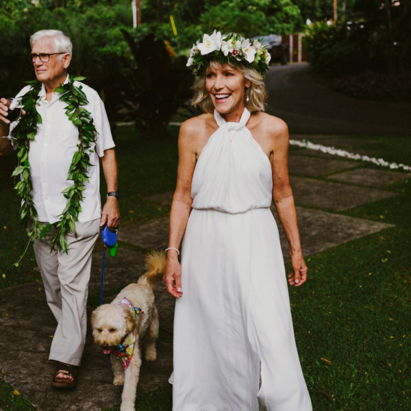 Wedding couple and dog approach the aisle in tropical gardens