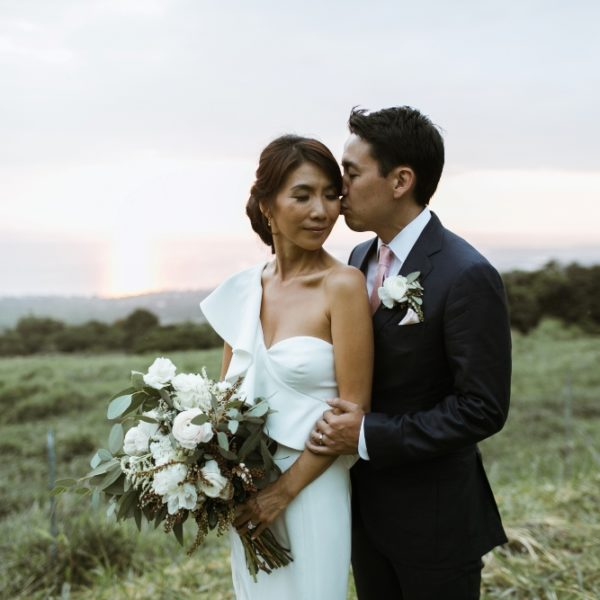 groom kissing bride with white bouquet at elegant Hawaii wedding