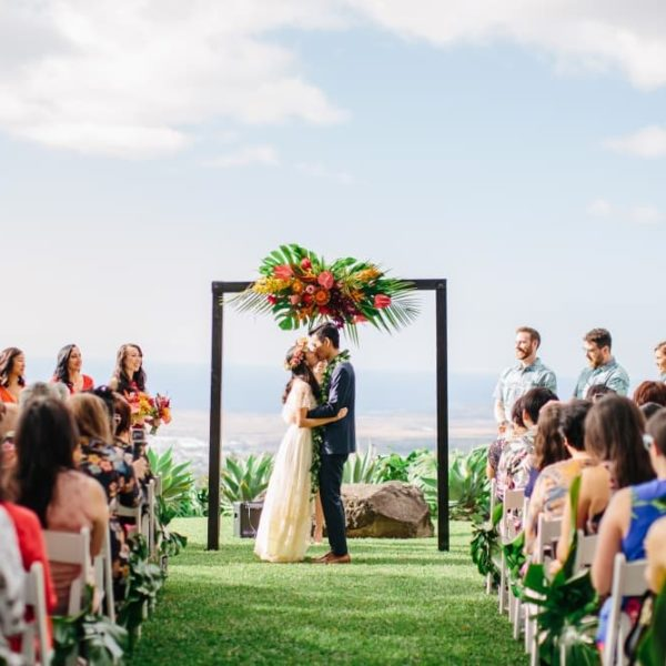 couple kissing under colorful archway at Big Island Wedding