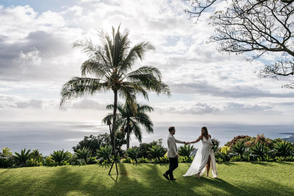 wedding couple holding hands by palm tree with ocean view
