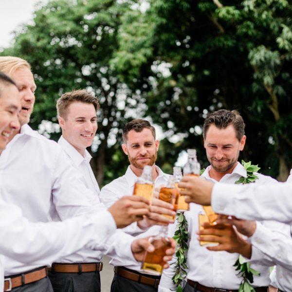 groomsmen cheers to the groom in Hawaiian wedding decor