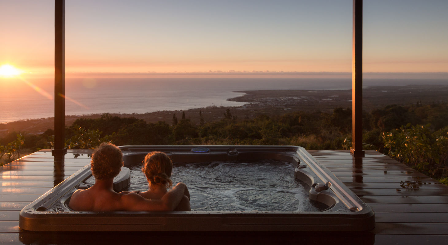 Couple in hot tub at Big Island Inn watching the sunset
