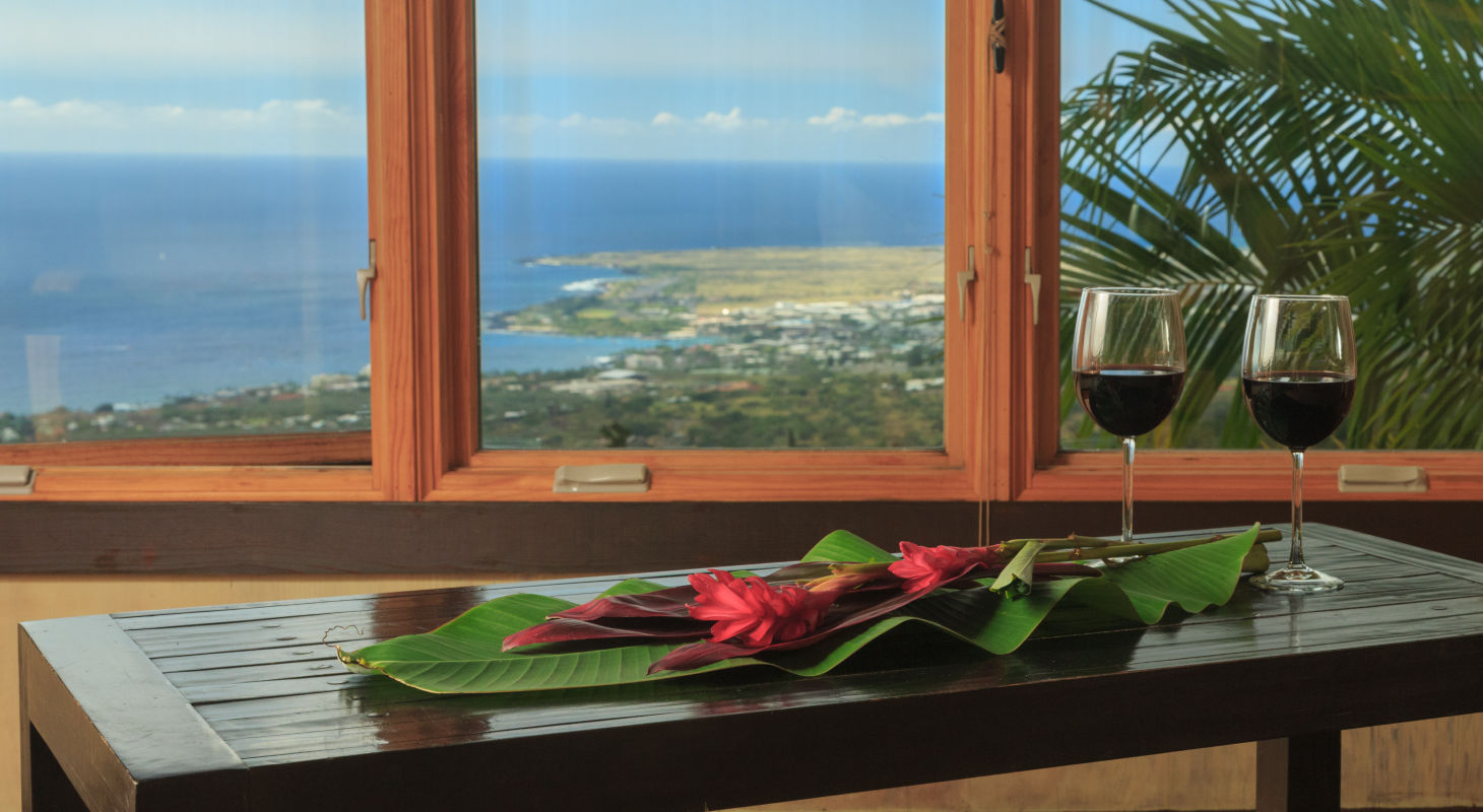 View of the Ocean from Holualoa Inn with wine glasses in forground