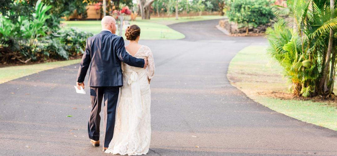Couple walking down a driveway after their fall hawaii destination wedding