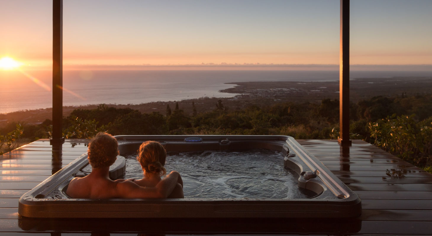 Couple sitting in a hot tub during their hawaii honeymoon