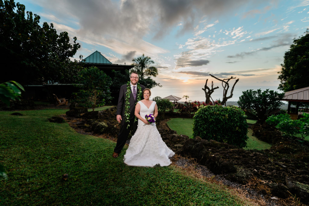 Elopement ceremony in tropical garden with sunset backdrop