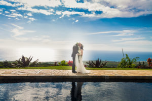 Couple traveling to elope in Hawaii by the pool