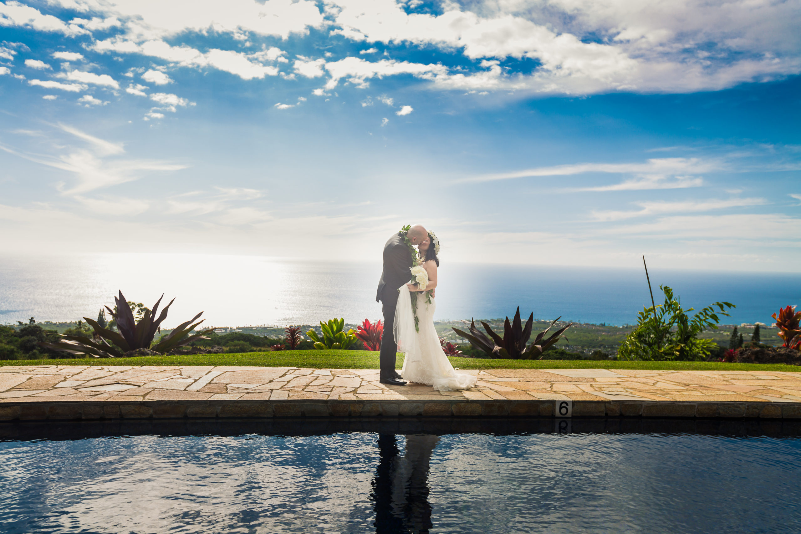 Bride and groom kissing by the pool in front of the ocean