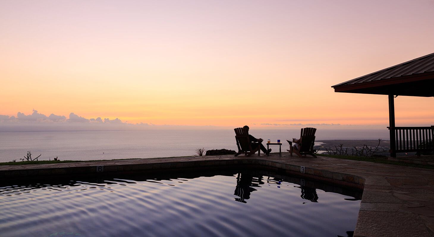 People in chairs by the pool overlooking the ocean at sunset