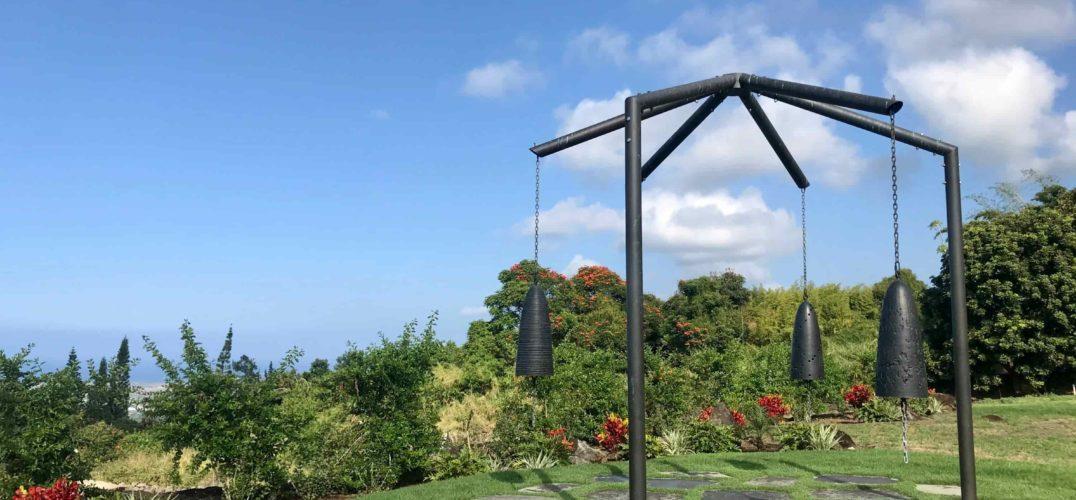 3 large bronze bells in front of flowers & ocean